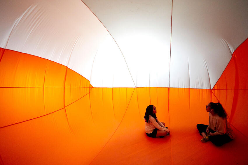 Two students sit inside an orange and white inflation