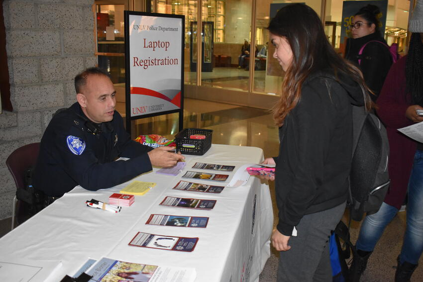 UNLV Police officer and student at Laptop Registration table