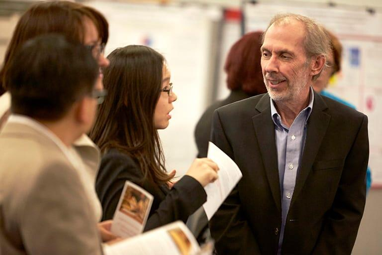 Faculty member chats with grad students