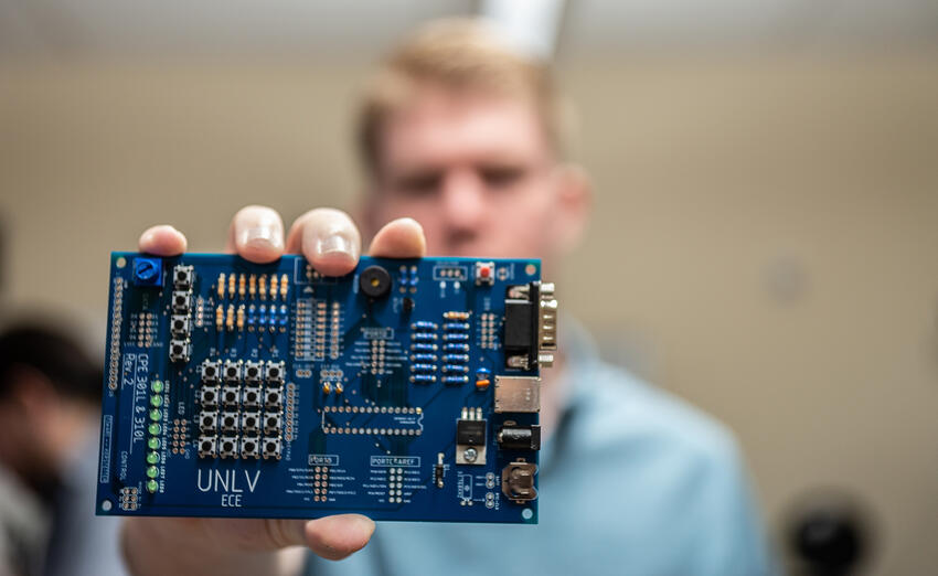 A student holding a circuit board to the camera.