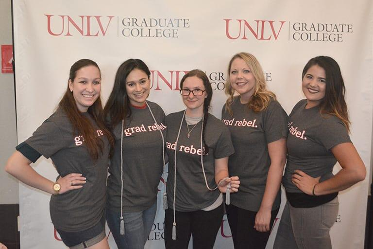 Students pose by a Graduate College backdrop.