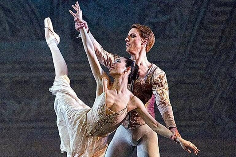 A man and woman dancing and performing classical ballet.