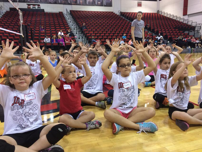 Kids in an auditorium with their hands up for volleyball.
