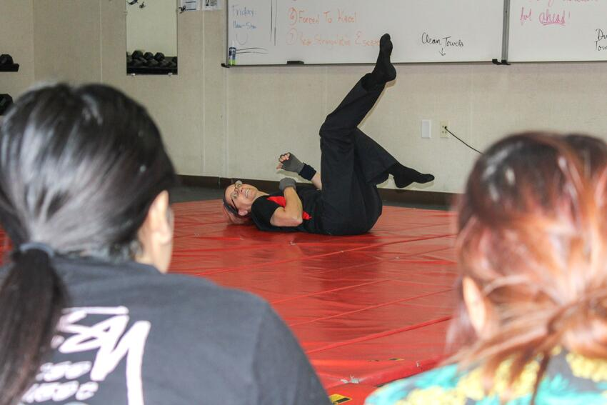An instructor on the floor demonstrating self defense.