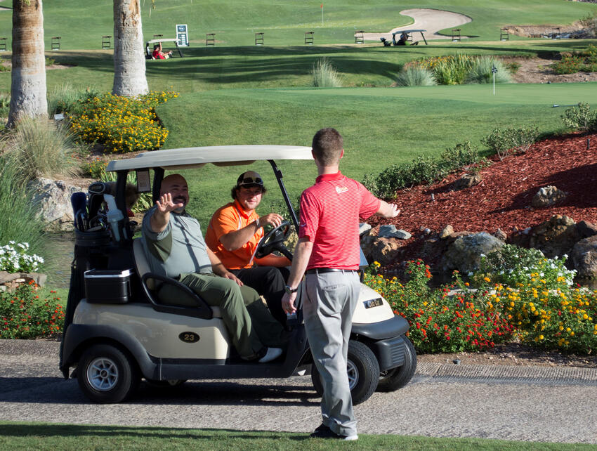 Three men with a golf cart on a golf course