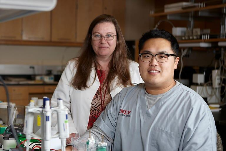 Faculty and grad student pose by lab equipment