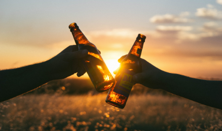 Two people holding beers.