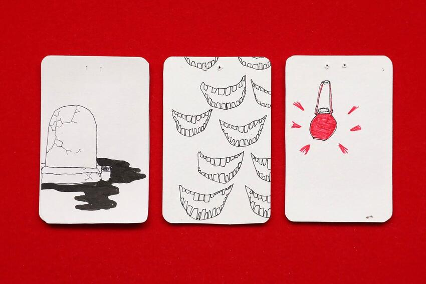 Three playing cards with art drawn on the backs.