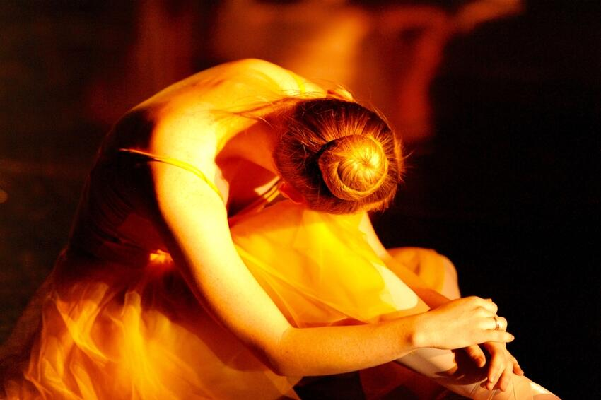 A dancer resting her head on her knee.