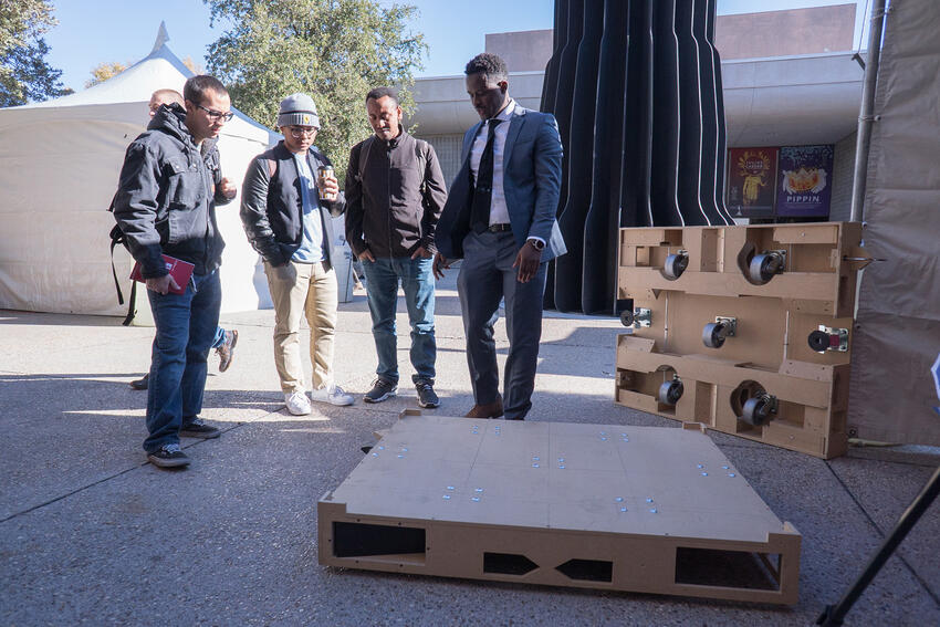 Group of men looking at a rolling platform designed for the Senior Design competition
