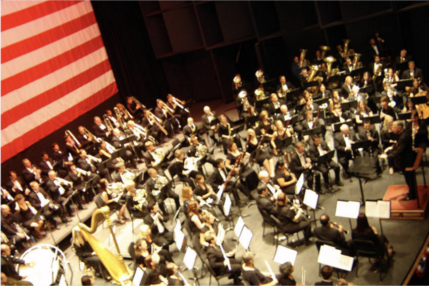 Musicians on a stage with a conductor