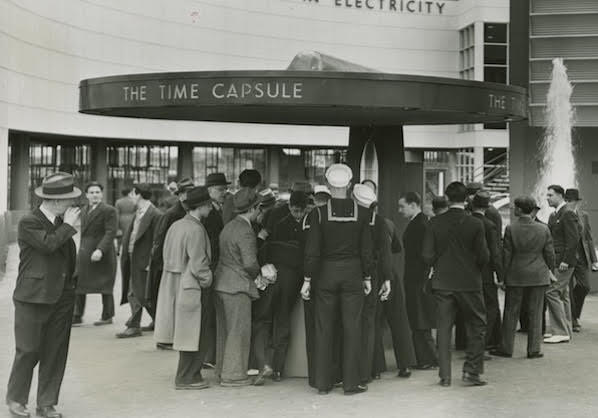 Black and white photo of crowd surrounding a time capsule.