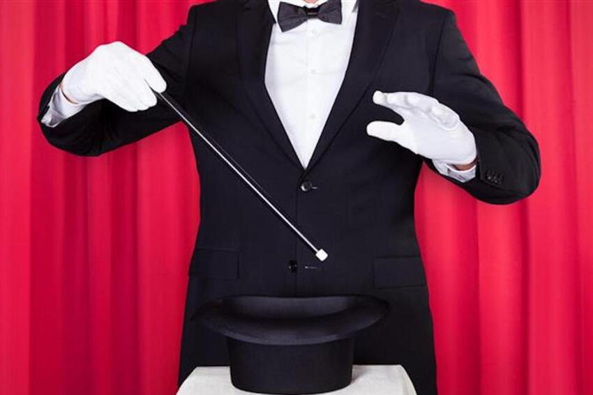 Magician in front of a red curtain with a wand pointed at a hat.