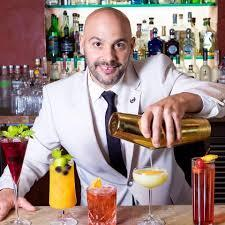 A man in a suit making cocktails.