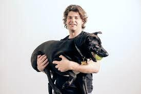 A man holding a dog with black fur with a ball in its mouth.