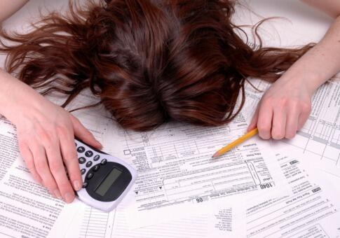 woman laying head down over tax papers