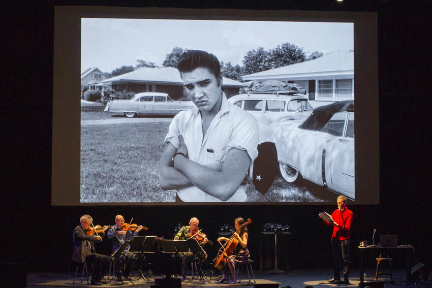 The Kronos Quartet performs in front of an image of Elvis.